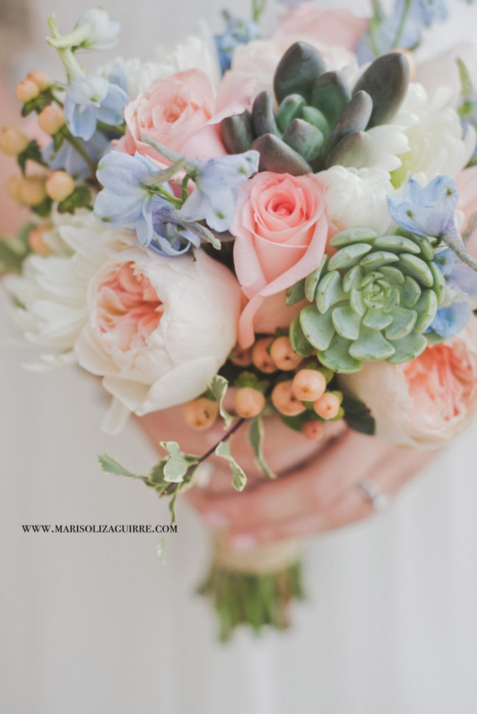 A blush and dusty blue bouquet with succulents is held by a bride. Photo by Marisol Izaguirre Photography.