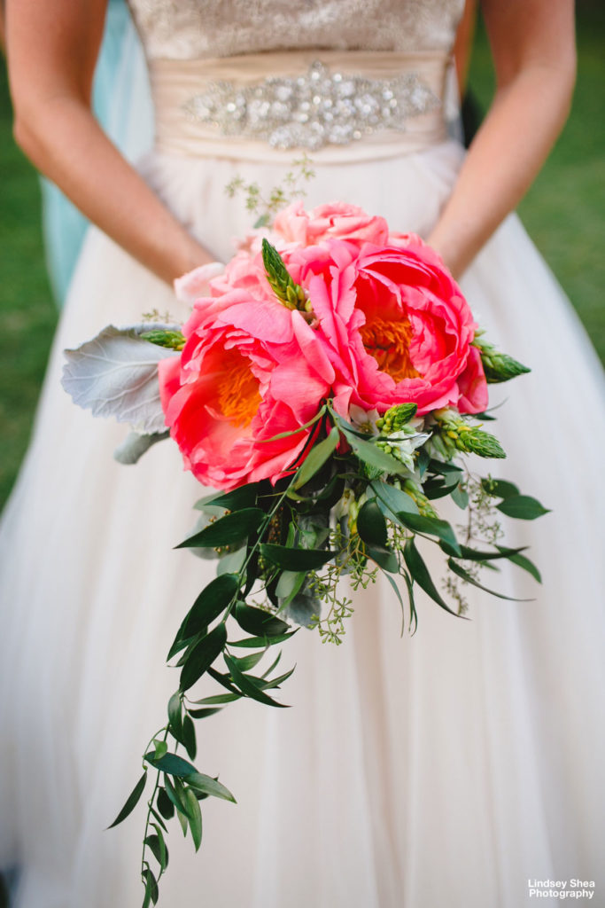 A bride holds her beautiful bouquet with large pink peonies and cascading greenery.