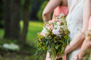 A garden style bouquet is held by a bridesmaid at an Austin wedding venue.