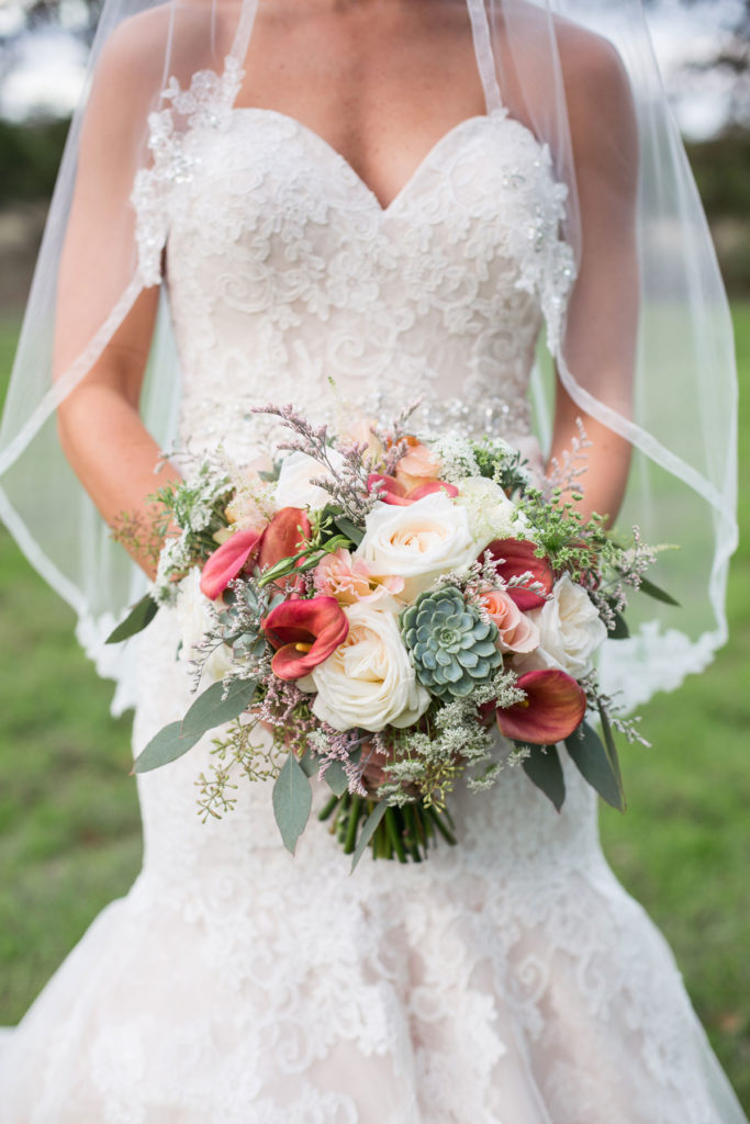 A bride in her gown and a veil holds a large, muted bridal bouquet at outdoor venue Kindred Oaks in Georgetown, Texas.