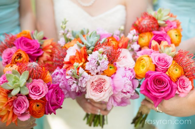 A close up of a bride and two bridesmaids holding bright pink and orange bouquets. Photo by Rasy Ran Photography.
