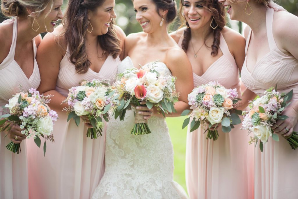 A bride and two bridesmaids wearing blush dresses smile at each other while holding their spring wedding floral bouquets.